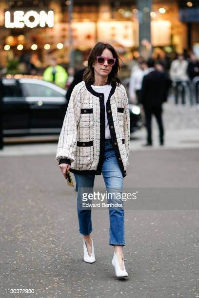 Guest wears a white tweed jacket, blue cropped pants, white shoes, sunglasses, outside Burberry, during London Fashion Week February 2019 on February...