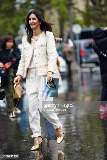 A guest wears a white tweed jacket white pants golden shoes a white top golden necklace earrings holds a golden bag outside Chanel during Paris...