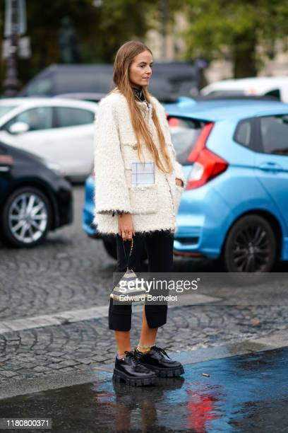 A guest wears a white wool jacket and golden and black striped pyramid Chanel bag black cropped pants black leather shoes outside Chanel during Paris...