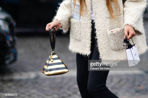 A guest wears a white wool jacket and golden and black striped pyramid Chanel bag outside Chanel during Paris Fashion Week Womenswear Spring Summer...