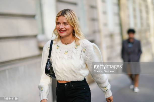 Guest wears a white wool knitted pullover, bejeweled shoes, a black bag, outside Alessandra Rich, during Paris Fashion Week - Womenswear Spring...