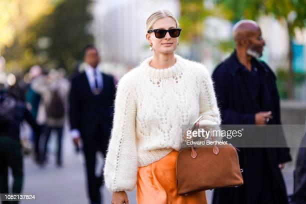 A guest wears a white wool pullover a brown bag outside Haider Ackermann during Paris Fashion Week Womenswear Spring/Summer 2019 on September 29 2018...