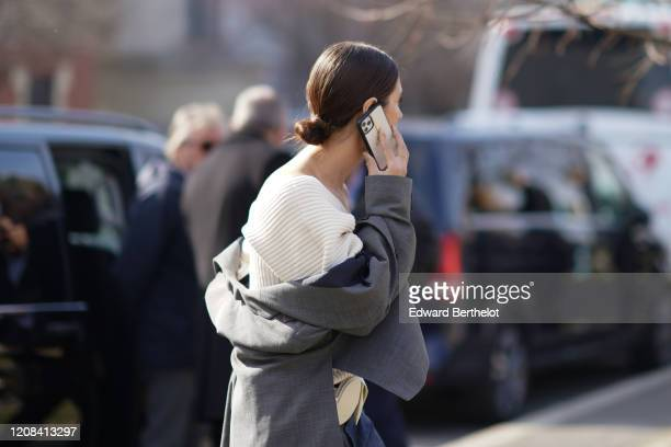 A guest wears a white wool pullover a gray jacket outside BOSS during Milan Fashion Week Fall/Winter 20202021 on February 23 2020 in Milan Italy