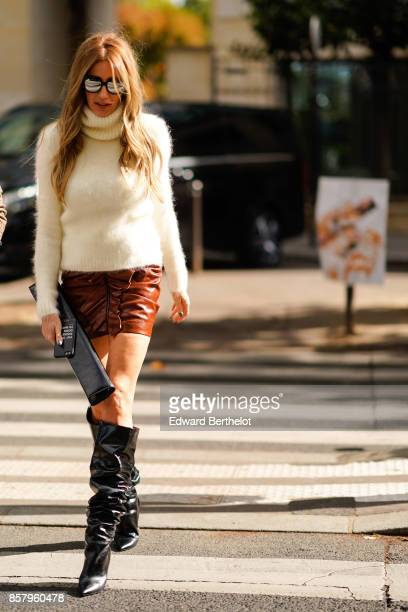 A guest wears a white wool turtleneck pull over sunglasses a short brown leather skirt black boots a long clutch outside Miu Miu during Paris Fashion...