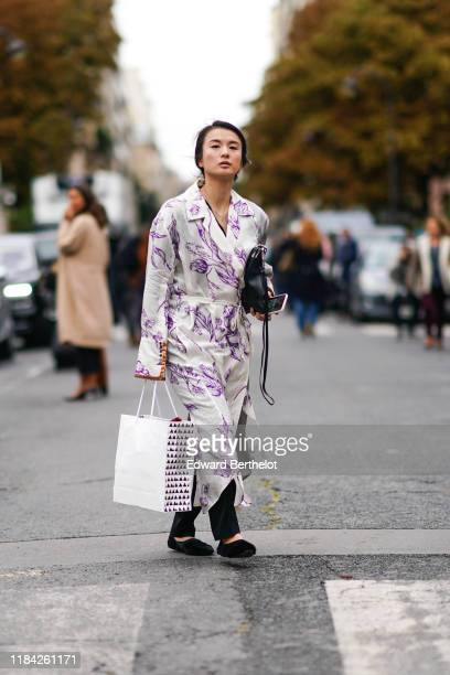 Guest wears a white wrap-over oversized dress with purple floral print, black pants, a black bag, black fluffy flat shoes, outside Margiela, during...