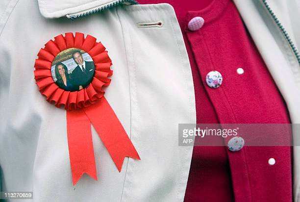 A guest wears a William and Kate rosette at a Tea in the Park event in the Middleton's home village of Bucklebury England on April 29 2011 AFP...