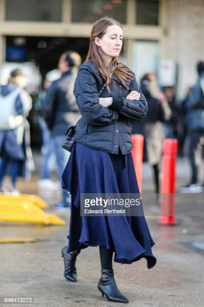 A guest wears a winter puffer coat a blue skirt and black shoes outside the Olivier Theyskens show during Paris Fashion Week Womenswear Fall/Winter...