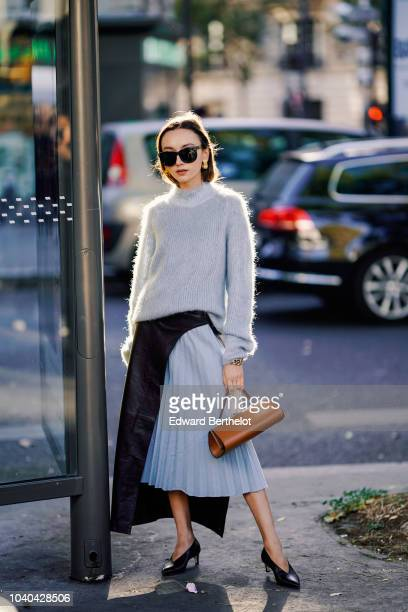 A guest wears a wool pullover a pale blue pleated skirt a brown leather bag outside Koche during Paris Fashion Week Womenswear Spring/Summer 2019 on...