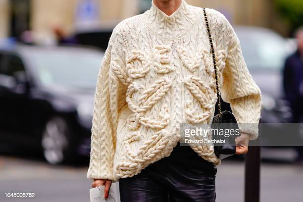 A guest wears a wool pullover outside Miu Miu during Paris Fashion Week Womenswear Spring/Summer 2019 on October 2 2018 in Paris France