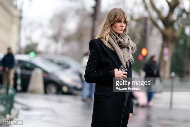 A guest wears a wool scarf and a black coat outside Alexandre Vauthier during Paris Fashion Week Haute Couture Spring Summer 2020 on January 22 2019...