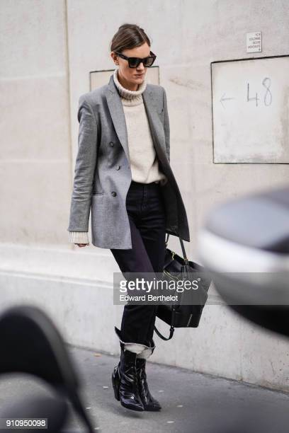 A guest wears a wool turtleneck a gray blazer jacket black pants black boots outside Elie Saab during Paris Fashion Week Haute Couture Spring/Summer...