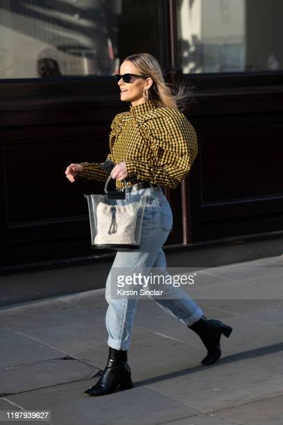 Guest wears a yellow and black check top with puff sleeves, light blue rolled up jeans, perspex bag and black boots during London Fashion Week Men's...