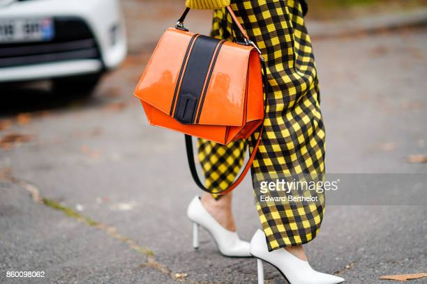 A guest wears a yellow and black checked skirt white stilettos an orange and dark brown bag outside Lanvin during Paris Fashion Week Womenswear...