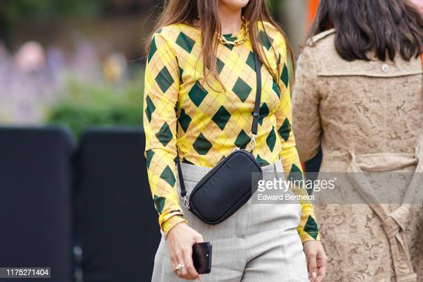 Guest wears a yellow and green checked pattern top, a black belt bag, gray pants, a golden necklace, during London Fashion Week September 2019 on...