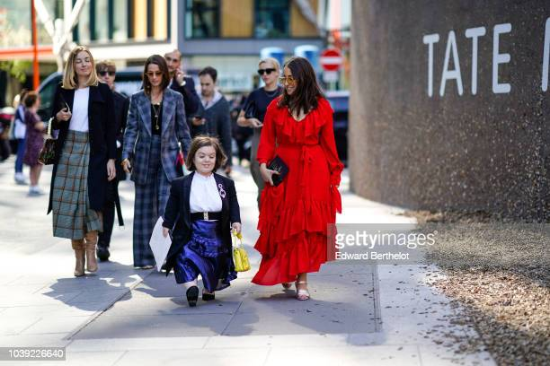 A guest wears a yellow bag a blue dress a blazer jacket a white shirt during London Fashion Week September 2018 on September 17 2018 in London England