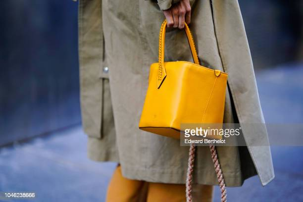 A guest wears a yellow bag outside APC during Paris Fashion Week Womenswear Spring/Summer 2019 on October 1 2018 in Paris France