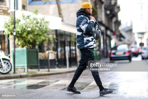 A guest wears a yellow beanie hat a bomber jacket a black hoodie black pants and black shoes outside the JOUR/NE show during Paris Fashion Week...