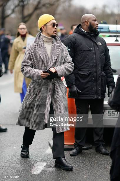 A guest wears a yellow beanie hat a gray coat black shoes outside Dior during Paris Fashion Week Menswear Fall Winter 20182019 on January 20 2018 in...