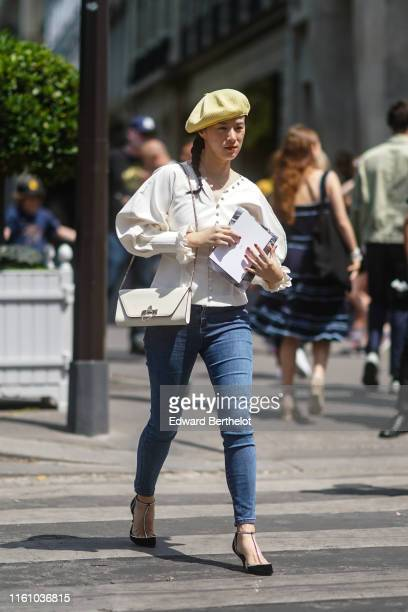 A guest wears a yellow beret hat a white frilly blouse with muttonleg sleeves a white bag blue denim skinny pants rhinestone embellished Tstrap pumps...