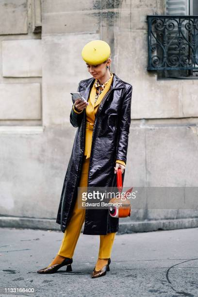 A guest wears a yellow beret hat a yellow pantsuit earrings a shiny black vinyl raincoat an orangeshaped handbag a shiny golden python pattern pointy...