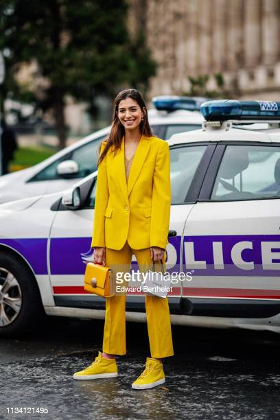 Guest wears a yellow blazer jacket, a yellow bag, yellow pants, sneakers, outside Chanel, during Paris Fashion Week Womenswear Fall/Winter 2019/2020,...