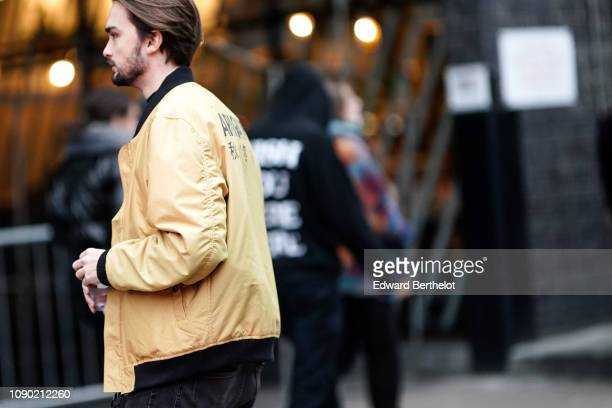 A guest wears a yellow bomber jacket from Arigato during London Fashion Week Men's January 2019 on January 05 2019 in London England