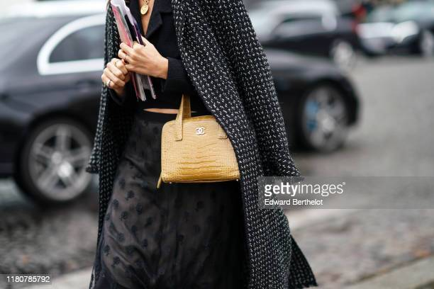 Guest wears a yellow Chanel bag, a tweed coat, a black mesh dress, outside Chanel, during Paris Fashion Week - Womenswear Spring Summer 2020, on...