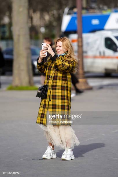 Guest wears a yellow checked pattern long coat, a crossbody bag, a mesh dress, white sneakers, outside Gauchere, during Paris Fashion Week -...