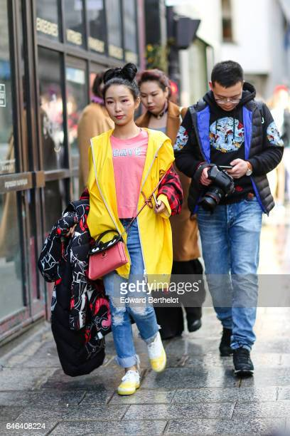 A guest wears a yellow coat a pink tshirt blue denim ripped jeans a pink bag and yellow shoes outside the AALTO show during Paris Fashion Week...