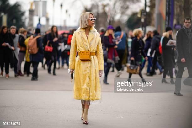 A guest wears a yellow coat a transparent plastic coat an orange belt bag outside Chanel during Paris Fashion Week Womenswear Fall/Winter 2018/2019...