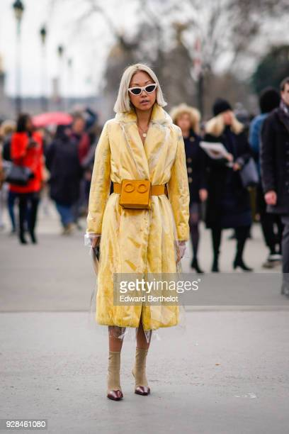 A guest wears a yellow coat a transparent plastic coat an orange belt bag outside Chanel during Paris Fashion Week Womenswear Fall/Winter 2018/2019...