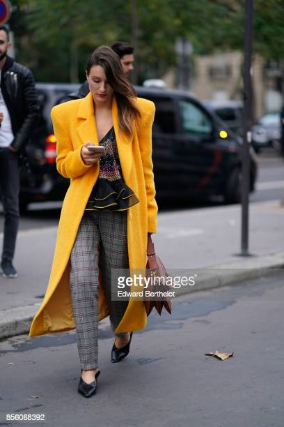 A guest wears a yellow coat tartan pants outside Rahul Mishra during Paris Fashion Week Womenswear Spring/Summer 2018 on September 30 2017 in Paris...