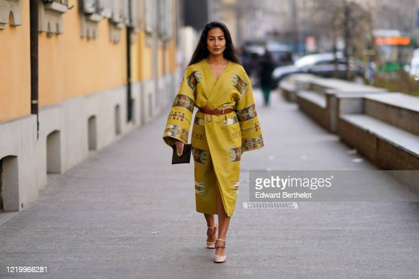Guest wears a yellow double breasted kimono dress with flared sleeves, a brown leather belt, shoes, outside Etro, during Milan Fashion Week...