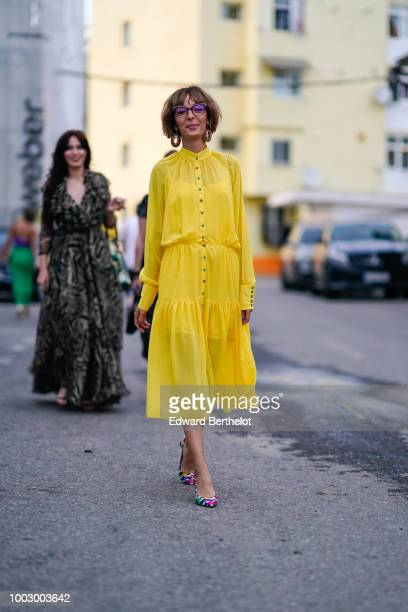 A guest wears a yellow dress earrings multicolor heels shoes during Feeric Fashion Week 2018 on July 20 2018 in Sibiu Romania