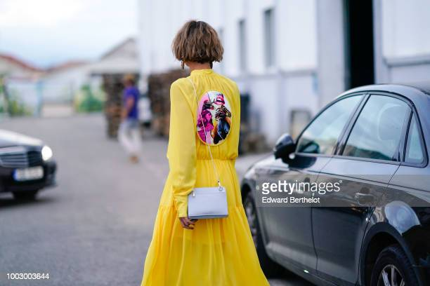 A guest wears a yellow dress with a multicolor patch a white bag during Feeric Fashion Week 2018 on July 20 2018 in Sibiu Romania