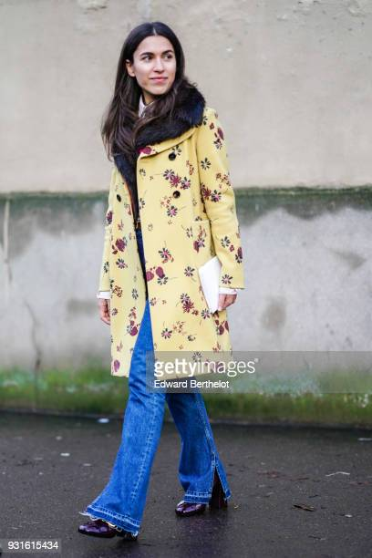 A guest wears a yellow floral print double breasted coat with a black fur collar a zipper hem flare blue jeans a white clutch patent shoes outside...
