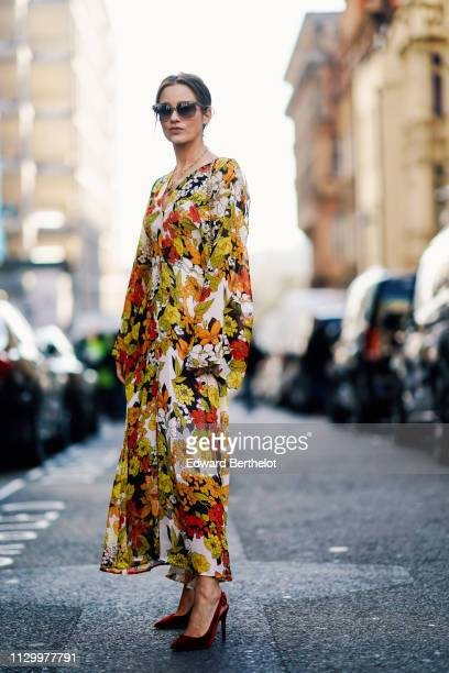 A guest wears a yellow floral print dress sunglasses during London Fashion Week February 2019 on February 15 2019 in London England