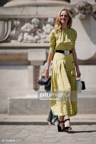 A guest wears a yellow flower print ruffle dress a belt with a silver heart black strap heels shoes outside the Chanel show during Paris Fashion Week...