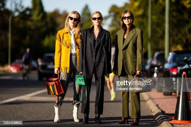 A guest wears a yellow fringed jacket a guest wears a black jacket a guest wears a green blazer jacket outside Hermes during Paris Fashion Week...