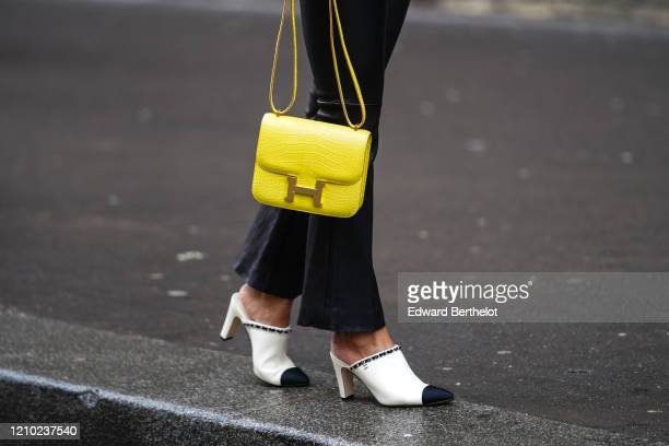 Guest wears a yellow Hermes crocodile pattern bag and Chanel shoes, outside Giambattista Valli, during Paris Fashion Week - Womenswear Fall/Winter...