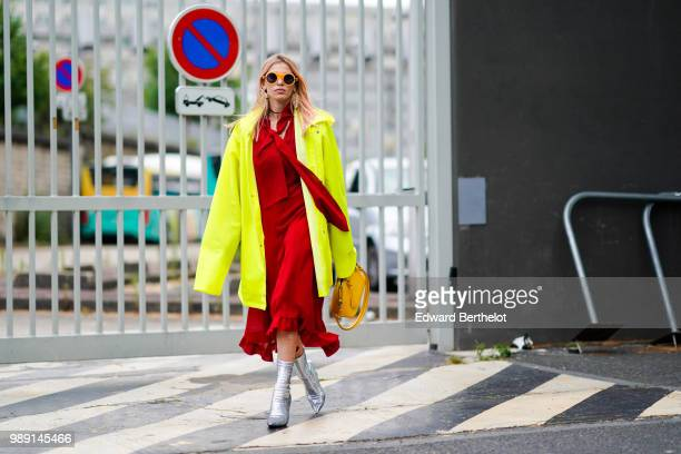A guest wears a yellow jacket a red dress silver boots a yellow bag outside Vetements during Paris Fashion Week Haute Couture Fall Winter 2018/2019...