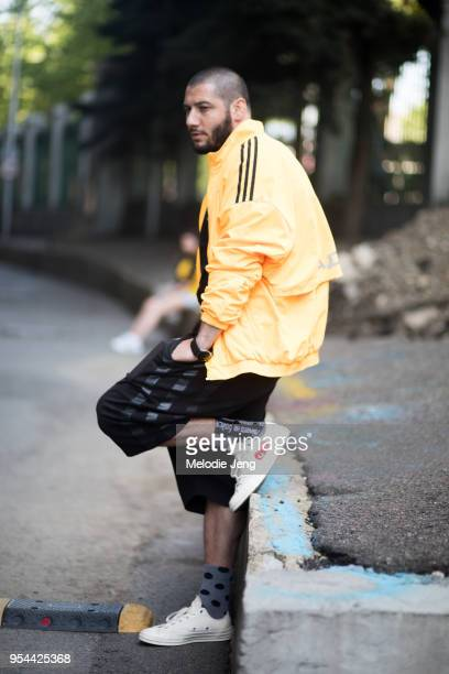 e65008b0f A guest wears a yellow jacket black shorts and white Comme des Garcons play  canvas sneakers