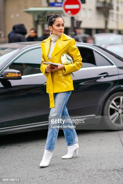 A guest wears a yellow jacket blue jeans white shoes during Paris Fashion Week Womenswear Fall/Winter 2018/2019 on March 1 2018 in Paris France