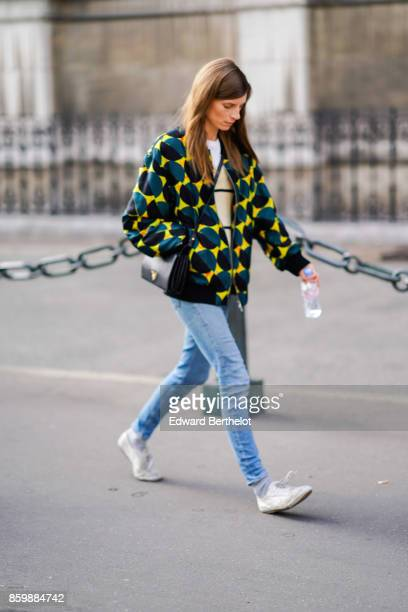 A guest wears a yellow jacket with black and blue impressionsa black bag blue jeans white sneakers outside the Dries Van Noten show during Paris...