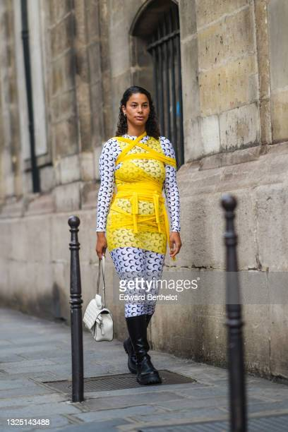 Guest wears a yellow mesh transparent short dress, over a Marine Serre moon monogram printed jumpsuit, black leather boots, a white bag, outside...