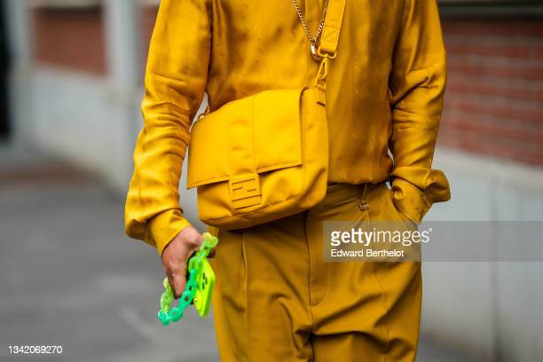 Guest wears a yellow mustard Fendi shirt, matching yellow mustard Fendi shorts, a yellow nylon Fendi crossbody bag, outside the Fendi fashion show...
