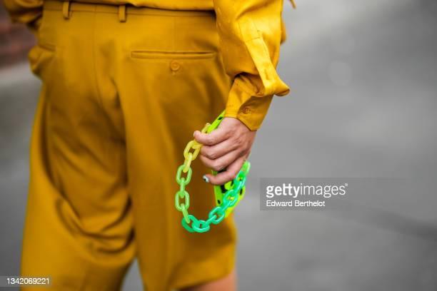 Guest wears a yellow mustard Fendi shirt, matching yellow mustard Fendi shorts, outside the Fendi fashion show during the Milan Fashion Week - Spring...