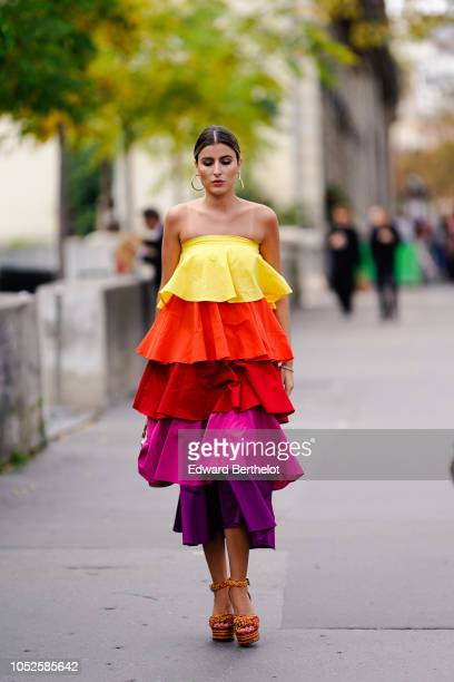 A guest wears a yellow orange red purple ruffled dress outside Issey Miyake during Paris Fashion Week Womenswear Spring/Summer 2019 on September 28...