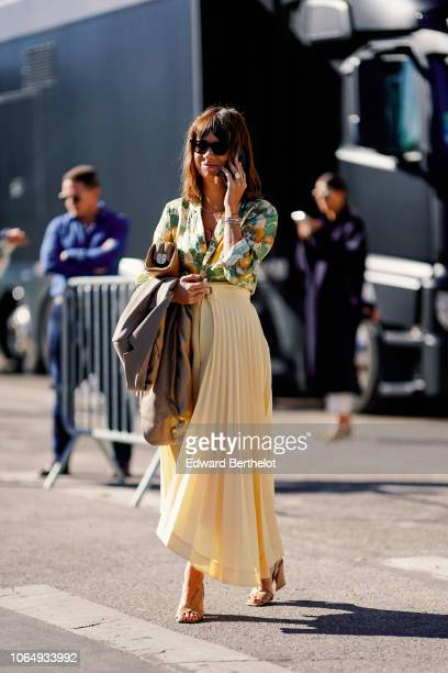A guest wears a yellow pleated skirt a floral print shirt shoes outside Margiela during Paris Fashion Week Womenswear Spring/Summer 2019 on September...