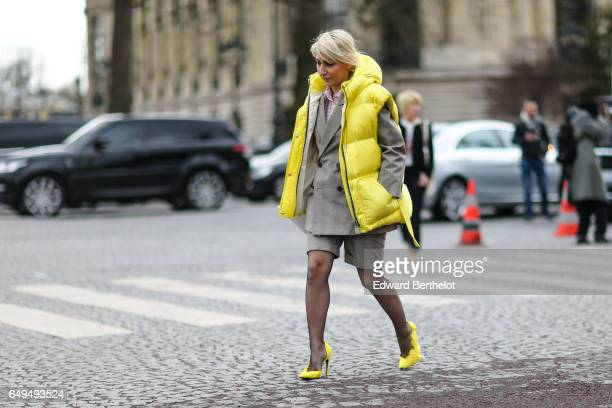 A guest wears a yellow puffer jacket and yellow shoes outside the Chanel show during Paris Fashion Week Womenswear Fall/Winter 2017/2018 on March 7...
